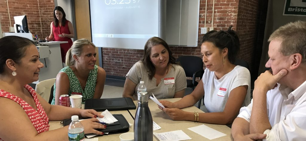 Class members Beatriz Oliveira, Kim Thomas, Patricia Andrade, Mary Ann Buckley, and Andy Tomolonis discuss the afternoon's legislation simulation activity during our local government day in August.